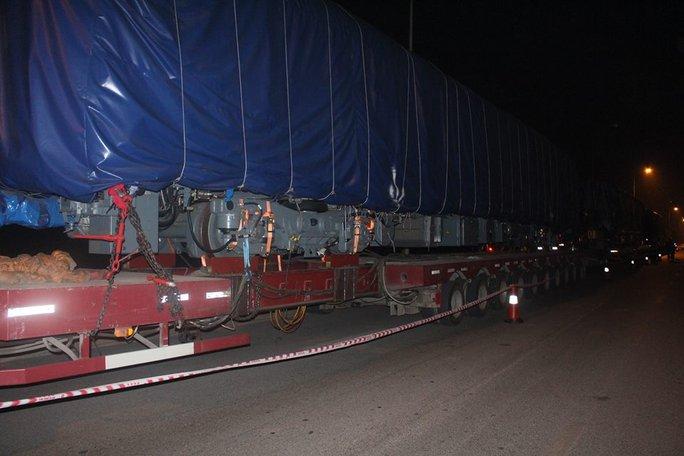 Đầu tàu và toa tàu được phủ bạt đen kín, chằng chặt bằng nhiều sợi xích lớn vào những chiếc xe siêu trường siêu trọng