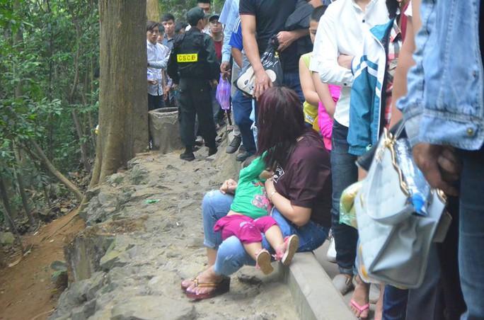 Một người phụ nữ phải tranh thủ cho con bú ngay tại đường lên núi Nghĩa Lĩnh