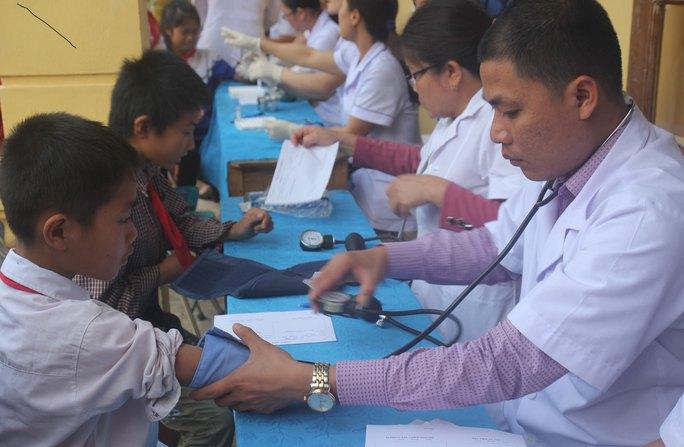 Các y - bác sĩ khám sàng lọc cho học sinh ở xã Hạnh Dịch vào sáng 22-2. Ảnh: HUỆ CẢNH