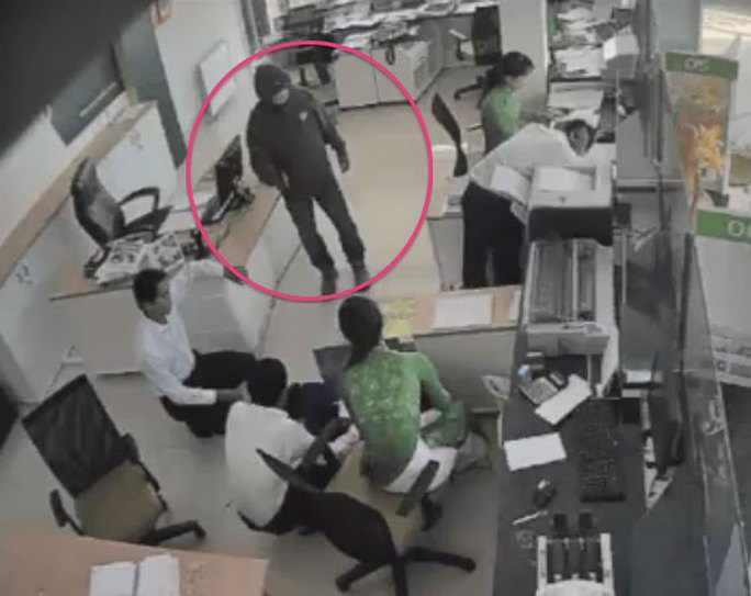 Tên cướp khống chế các nhân viên ngân hàng. (Ảnh từ camera tại Chi nhánh Vietcombank thị xã Duyên Hải)