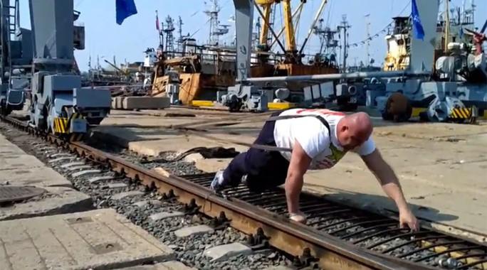 Ivan Savkin dùng sức kéo cần trục cảng nặng 312 tấn. Ảnh: Ruptly