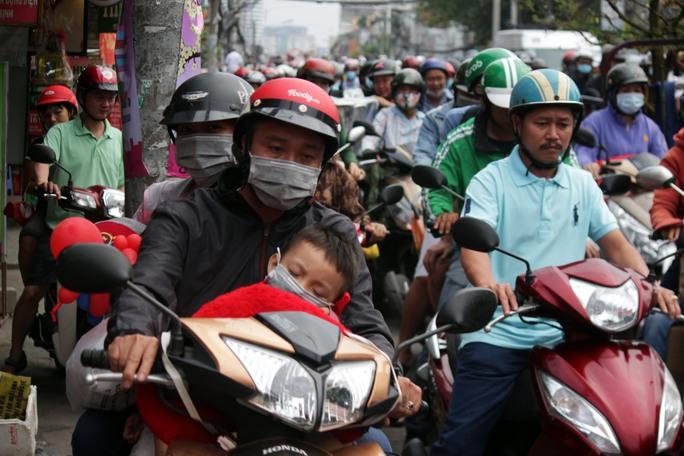 Người đi xe máy mệt mỏi vì kẹt xe kéo dài.