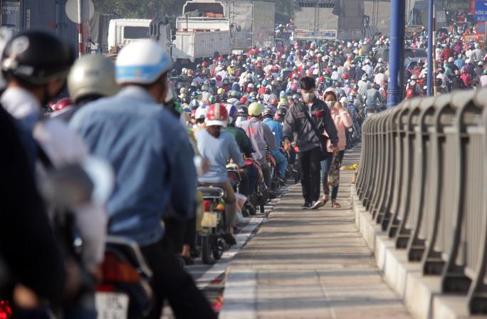Một nam thanh niên không còn kiên nhẫn chờ đợi trong đám kẹt xe, vác xe đạp lên vỉa hành lang cầu để chạy