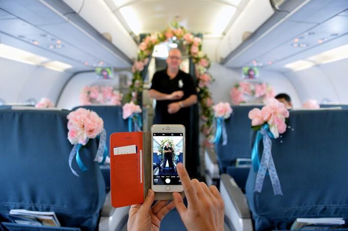 Một hành khách đến từ châu Âu thích thú với hoa trang trí trên máy bay.