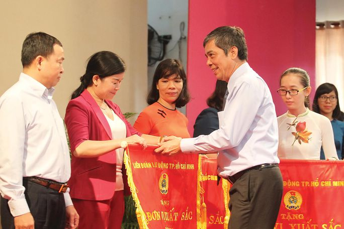 Ông Nguyễn Văn Khải, Phó Chủ tịch Thường trực LĐLĐ TP HCM, tặng cờ thi đua xuất sắc cho các đơn vị tiêu biểu Ảnh: HOÀNG TRIỀU