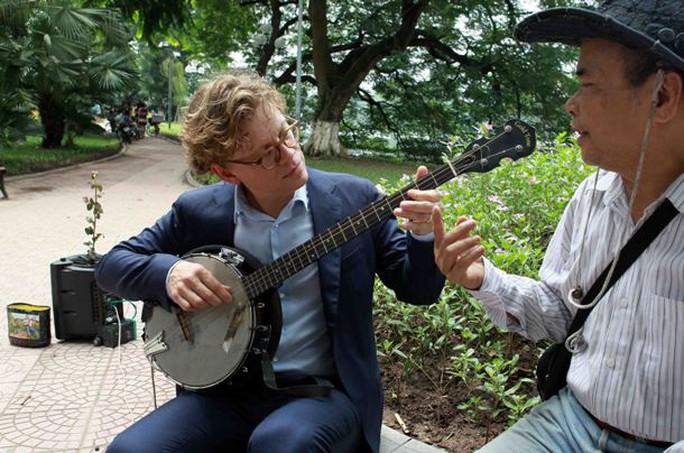 Đại sứ Högberg chơi thử đàn của người chơi đàn bên hồ Hoàn Kiếm. Đại sứ là người yêu âm nhạc, có giọng hát rất hay, còn phu nhân Anna Högberg là một giáo viên dạy nhạc - Ảnh: Trần Việt