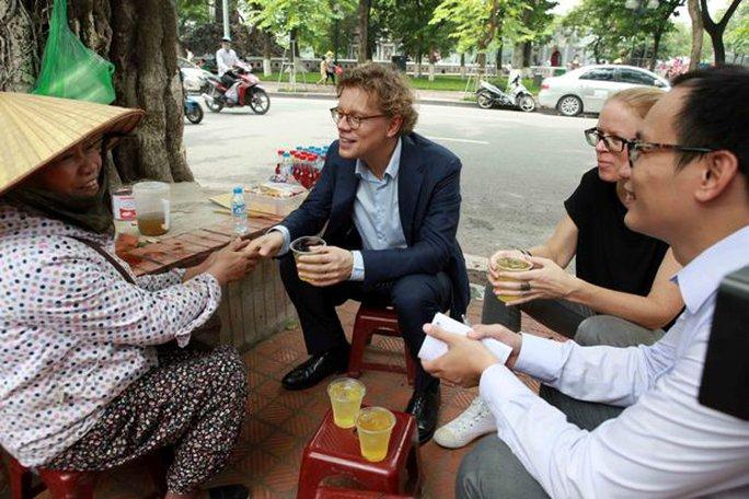 Đại sứ Thụy Điển Pereric Högberg trò chuyện với một chủ hàng trà đá bên bờ hồ Hoàn Kiếm - Ảnh: Trần Việt