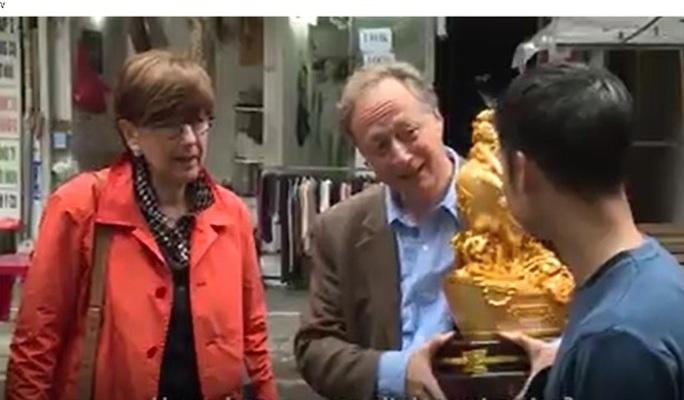 Sau khi mua được bức tượng gà cho năm mới, Đại sứ, Trưởng đại diện Phái đoàn Liên minh châu Âu tại Việt Nam Bruno Angelet bê nó đi cùng khắp phiên chợ - Ảnh: Đại sứ mặc cả mua một cây quất trong phiên chợ