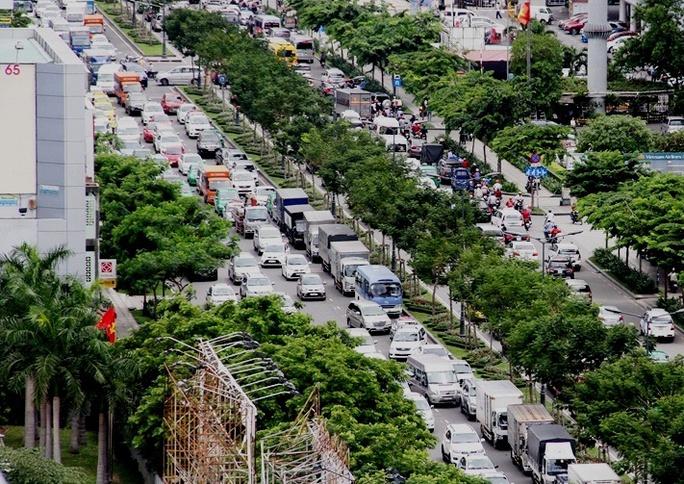Còn bên ngoài, dòng ô tô cũng nối đuôi nhau kéo dài, trong khi xe máy phải luồn lách giữa các hàng ô tô hoặc leo lên vỉa hè để lưu thông.