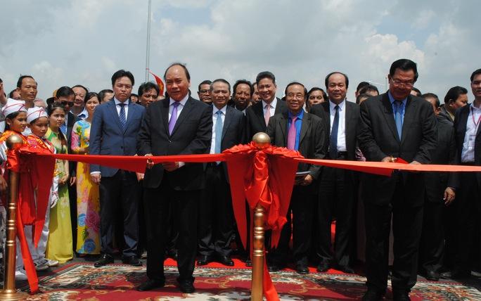 Thủ tướng Nguyễn Xuân Phúc (bìa trái) cùng Thủ tướng Hun Sen cắt băng khánh thành cầu Long Bình-Chrey Thom vào sáng 24-4.