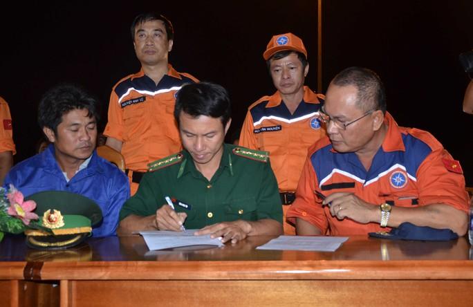 Thuyền trưởng Phan Xuân Sơn trên tàu SAR 412 Thuyền trưởng Sơn (ngoài cùng bên phải) trong lần bàn giao ngư dân gặp nạn cho bộ đội biên phòng.