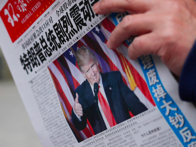 Một người dân Trung Quốc đọc một tờ báo có hình ông Trump trên trang bìa. Ảnh: AP