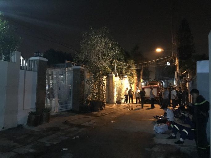 Lực lượng chức năng đứng trước căn nhà nơi xảy ra vụ cháy lúc rạng sáng