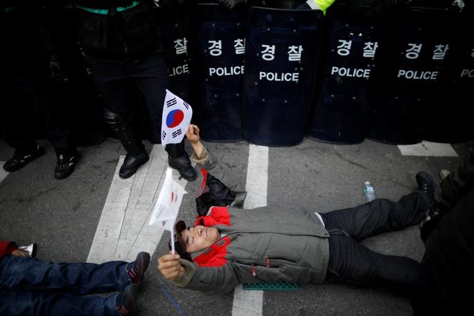 Một người ủng hộ bà Park Geun-hye nằm trước cảnh sát chống bạo động trong cuộc biểu tình gần Tòa án Hiến pháp ở Seoul hôm 10-3 Ảnh: Reuters