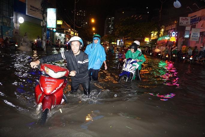 Nước chảy như lũ ở TP HCM sau cơn mưa lớn - Ảnh 6.