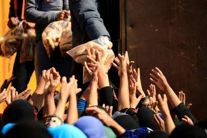 Những người được giải thoát hôm 14-3 được tiếp tế lương thực. Ảnh: Reuters