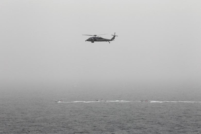 Trực thăng Mỹ bay phía trên ba chiếc thuyền cao tốc của lực lượng Vệ binh Cách mạng Hồi giáo Iran tại eo biển Hormuz hôm 21-3. Ảnh: REUTERS