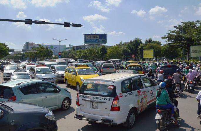 Tại khu vực cổng sân bay Tân Sơn Nhất cùng các tuyến đường dẫn vào 2 nhà ga quốc nội và quốc tế của sân bay này, ô tô xếp ken đặc, chậm chạp di chuyển. Trong ảnh: Cảnh hỗn loạn trên đường Trường Sơn - đoạn qua cổng sân bay Tân Sơn Nhất