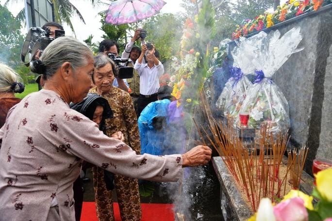 Người dân đội mưa thắp hương tưởng niệm vụ thảm sát. Ảnh: Tử Trực