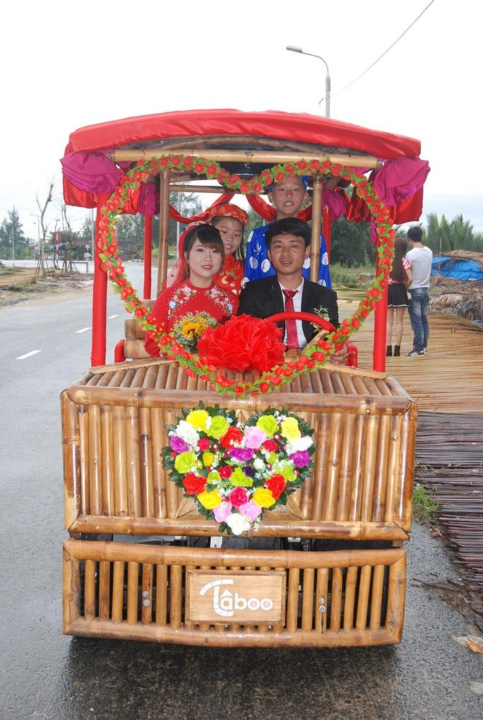 Cô dâu chú rể hạnh phúc trên chiếc xe điện làm bằng tre Ảnh: Võ Tấn Tân