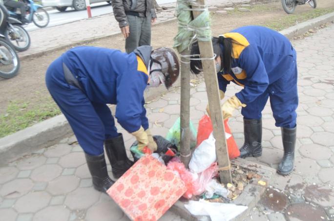 Công nhân nhắc nhở người dân bỏ rác tập trung vào một nơi và thu gom về một đống