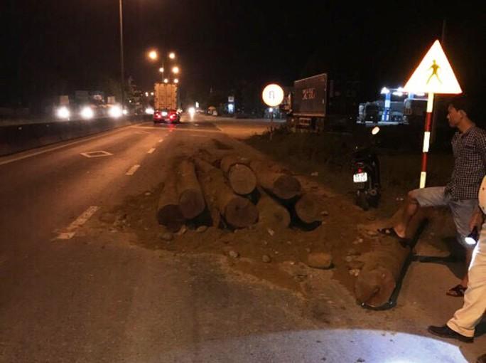 Số gỗ lậu được ngụy trang trong đất đổ xuống hiện trường Ảnh: CTV