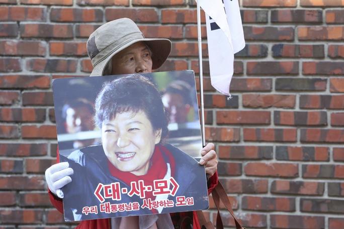 Một người ủng hộ bà Park Geun-hye trước nhà riêng của bà ở thủ đô Seoul ngày 15-3 Ảnh: AP