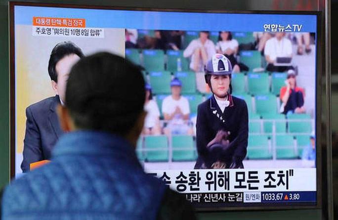 Truyền hình Hàn Quốc đưa tin về vụ bắt giữ cô Chung Yoo-ra hôm 2-1-2017 Ảnh: AP
