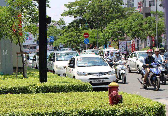 Xe taxi đậu thành hàng dưới lòng đường Nguyễn Văn Cừ...