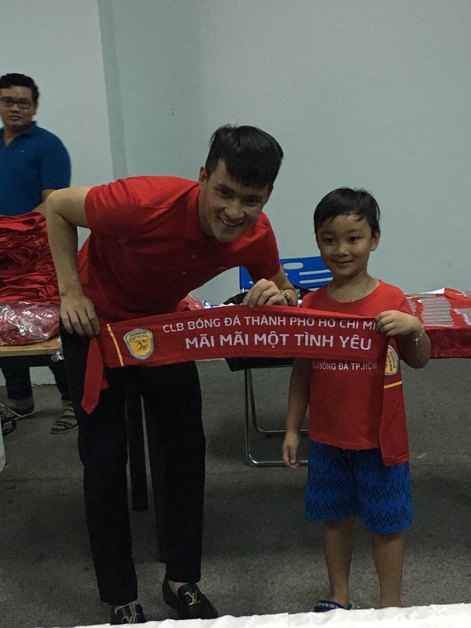 Cựu tiền đạo số 1 tuyển Việt Nam hào hứng chụp ảnh kỷ niệm cùng em nhỏ 6 tuổi đến mua áo cổ vũ đội bóng