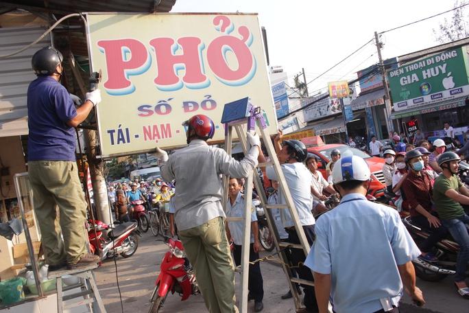Khi thấy đoàn kiểm tra, chủ quán phở trên đường Hồ Học Lãm đã tự nguyện dỡ các biển quảng cáo, mái che lấn chiếm lòng lề đường.