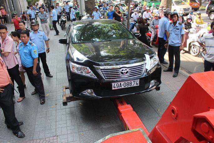Chiếc xe Camry đậu trên vỉa hè trước một ngân hàng trên đường Tôn Đức Thắng bị niêm phong, cẩu về trụ sở cơ quan chức năng để xử lý.