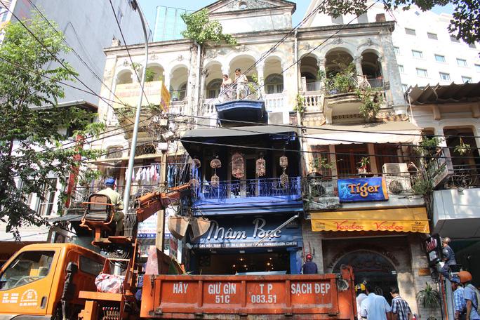 Trên đường Hồ Tùng Mậu, phát hiện nhiều cửa hàng có gian hàng, biển hiệu, mành che lấn vỉa hè, ông Hải chỉ đạo đoàn liên ngành cho máy kéo dọn sạch, giải tỏa không gian, trả lại mỹ quan đô thị.