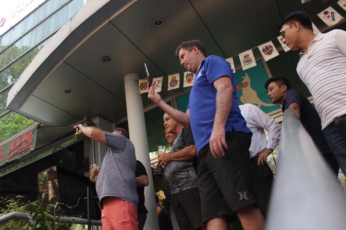 Những người nước ngoài đang ngồi uống bia tỏ ra bất ngờ, thích thú dùng điện thoại quay phim, chụp hình cảnh lực lượng chức năng tháo dỡ.