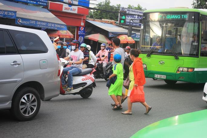 Nhiều người phải qua đường trước đầu xe ô tô đang lưu thông nên rất nguy hiểm