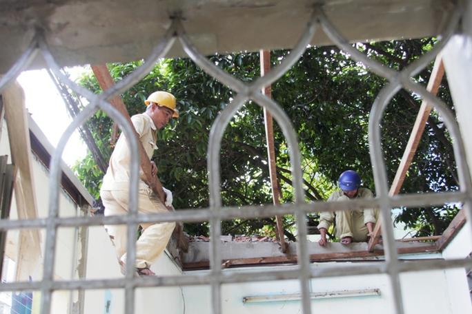 Công nhân tháo xong phần mái và bắt đầu tháo dỡ xà gỗ