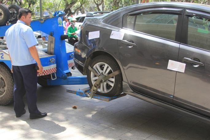 Xe cẩu sẽ nâng một đầu và kéo xe vi phạm, tài xế phải trả tiền cẩu xe