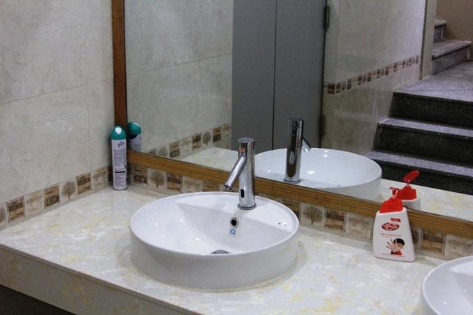 Bồn rửa tay tự động cùng xà bông và bình xịt khử mùi