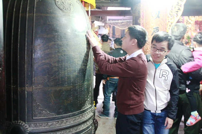 Nhiều du khách đã tranh thủ vào trong đền sờ vào chuông đồng để xin may mắn
