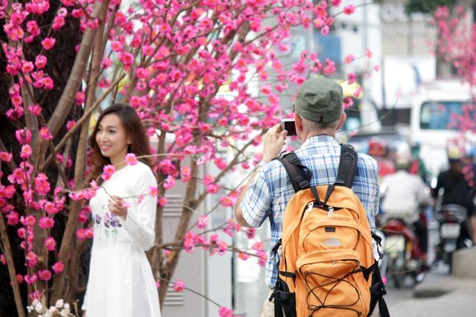 Một du khách nước ngoài thích thú ghi lại hình ảnh thiếu nữ mặc áo dài thướt tha tạo dáng bên hoa đào.