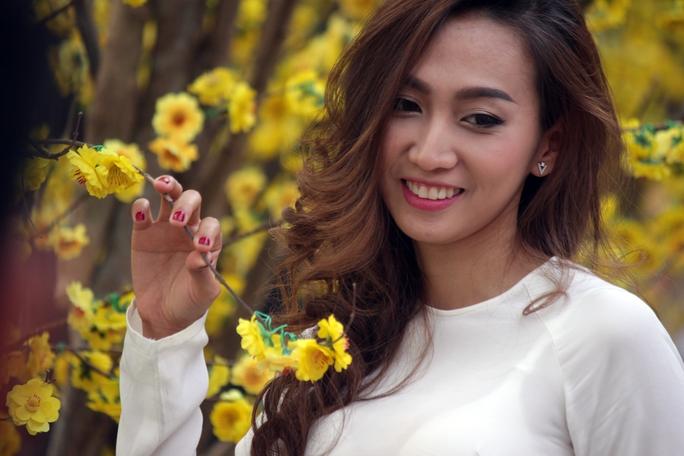 Một cô gái tạo dáng dịu dàng bên hoa mai với tà áo dài trắng truyền thống tinh khôi.