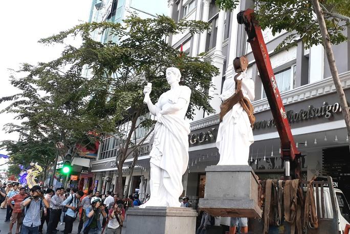 Lực lượng chức năng cẩu bức tượng lấn chiếm vỉa hè trước một khách sạn trên đường Nguyễn Huệ, phường Bến Nghé, quận 1, TP HCM Ảnh: SỸ ĐÔNG