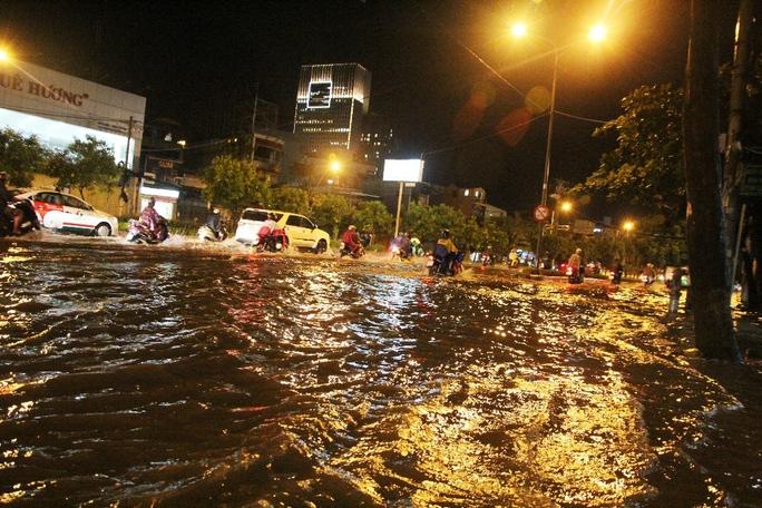 Nước chảy như lũ ở TP HCM sau cơn mưa lớn - Ảnh 1.