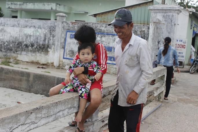 Hai anh em ở Thổ Chu đang ngồi ngoài cảng để chờ ba mẹ đánh cá trở về