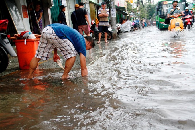 Người dân TP HCM bì bõm sau cơn mưa lớn - Ảnh 3.