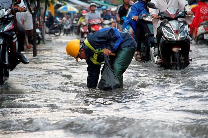 Người dân TP HCM bì bõm sau cơn mưa lớn - Ảnh 2.
