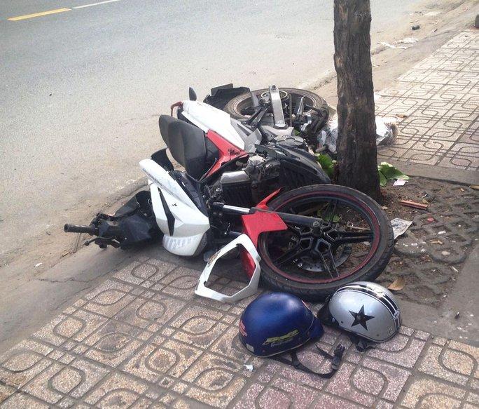 Chiếc xe máy nằm chỏng chơ dưới gốc cây ven đường sau cú tông