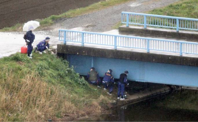 Nhân viên điều tra tại nơi tìm thấy thi thể bé Nhật Linh hôm 26-3. Ảnh: Kyodo