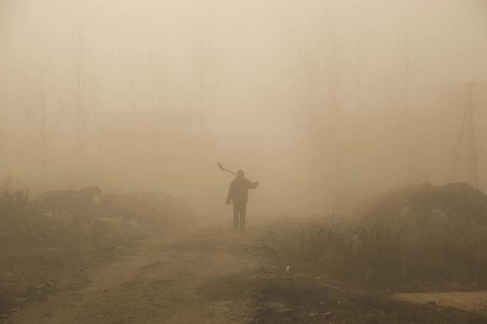Một nông dân trong làn khói mù khủng khiếp. Ảnh: AP