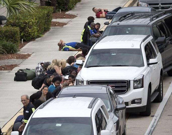 Mọi người tìm nơi trú ẩn trong khi cảnh sát xử lý vụ việc tại hiện trường. Ảnh: AP